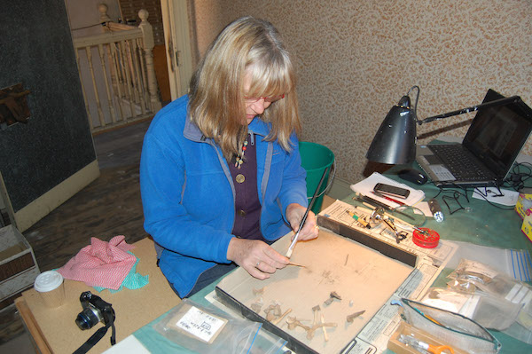 Conservator Linda Clark cleaning artefacts