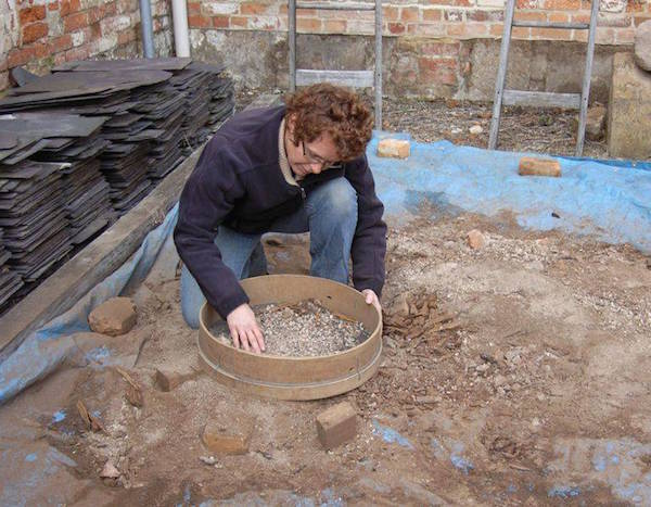 The artefact-rich soil from the cell is sieved to reveal more treasures